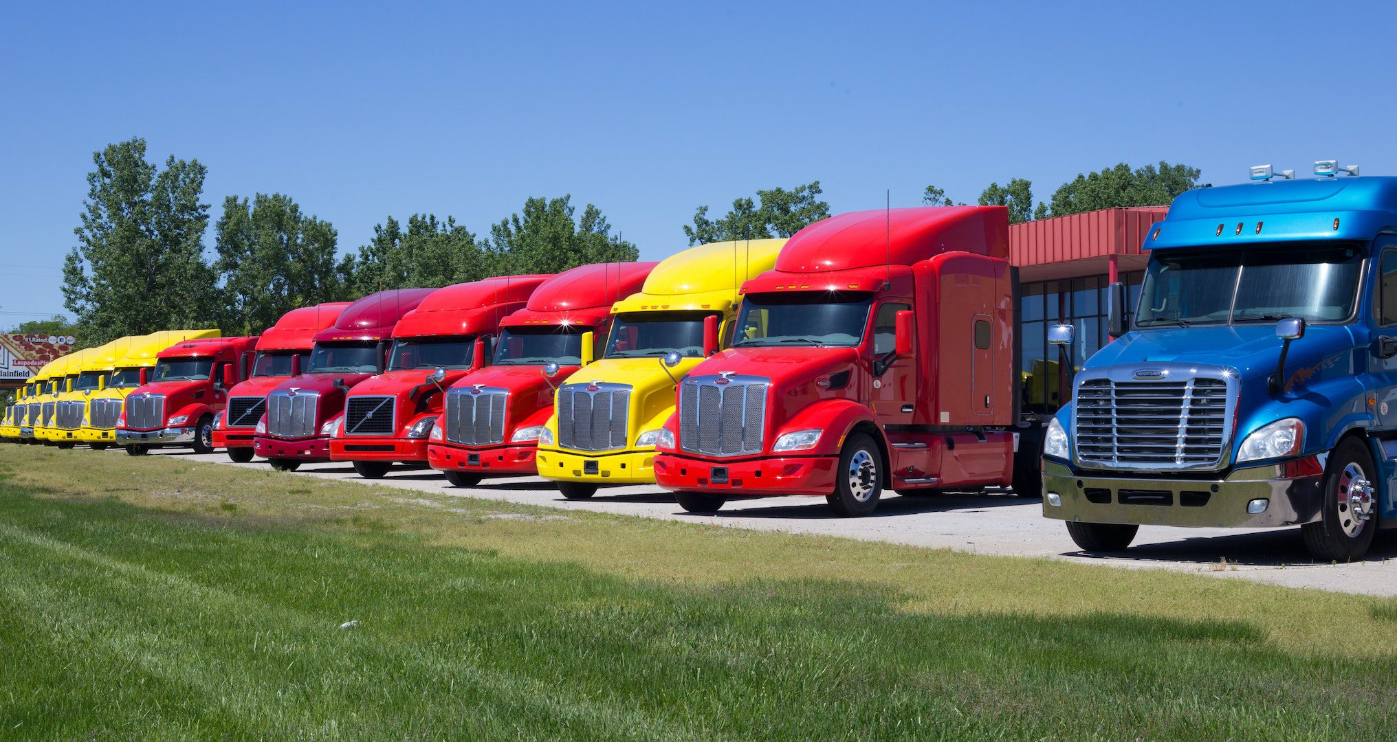 red, yellow, and blue semi trucks lined up