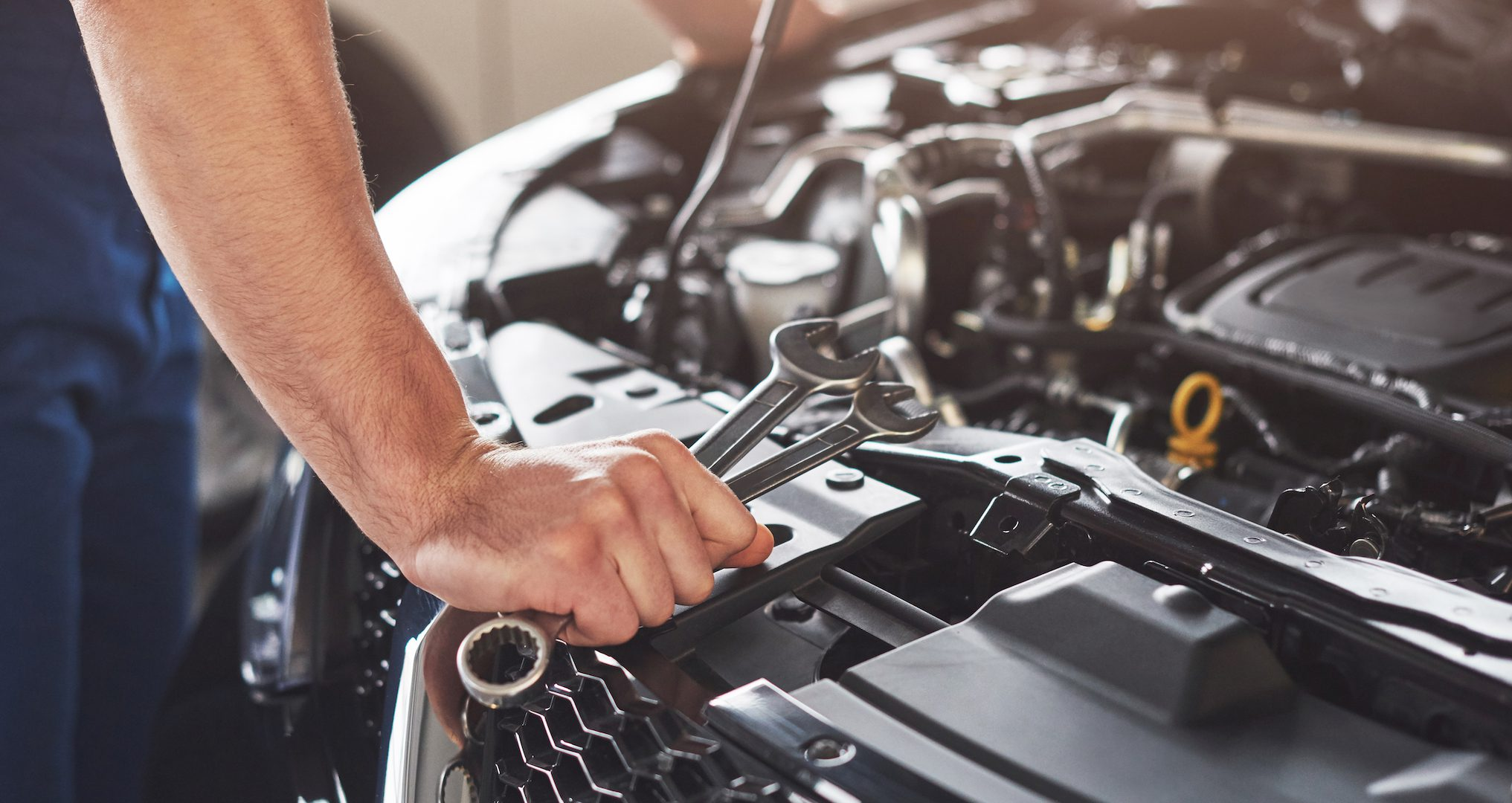 man leaning over car working on engine